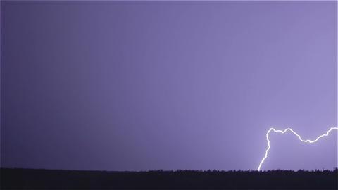 Various lightning bolts strike forest night landscape, sound included Footage