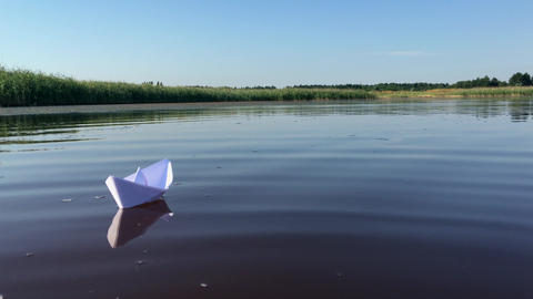 Small paper boat floats away on the river Footage