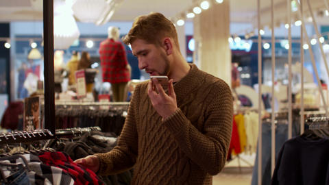 Young man chooses clothes and talking on the phone Footage