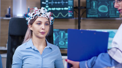 Female patient reading brain data from clipboard holded by female doctor ビデオ