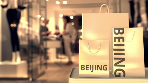 Shopping bags with BEIJING text against blurred store. Chinese retail related Footage