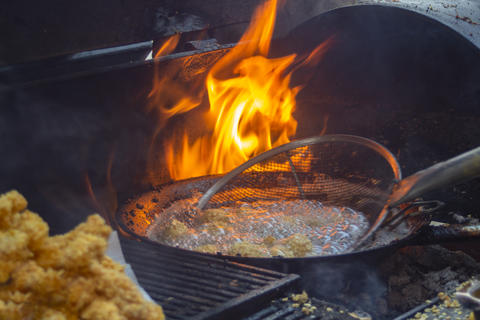 Wok on fire in a mobile kitchen Photo