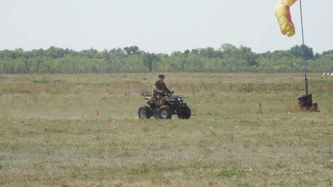 Man in camouflage uniform rides on an ATV Footage
