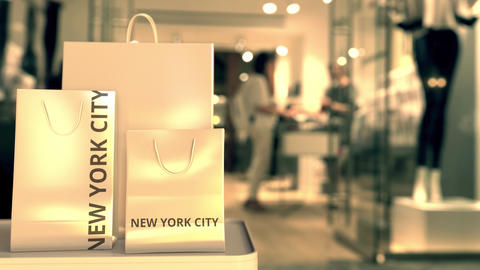 Shopping bags with NEW YORK CITY text against blurred store. American retail Footage