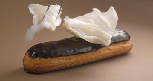 Confectioner adds white chocolate pieces to the eclair, making dessert with ビデオ
