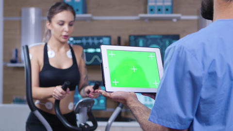 Doctor holding tablet with green screen in front of athlete Footage