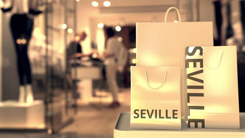 Paper shopping bags with SEVILLE text against blurred store. Spanish shopping GIF