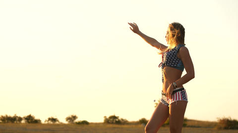 A young slender woman staring to the sunset rays light breeze sways her hair She Footage