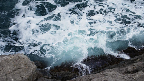 SLOW MOTION Top view to the seafoam with splashes of the waves Wet cliff at the GIF