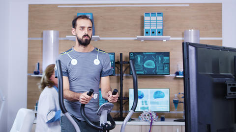 Male athlete running with electrodes attrached to his body Footage