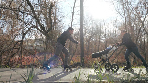 Sporty cheerful parents enjoy a walk in a warm park on roller skates with a baby Footage