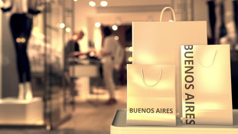 Paper shopping bags with BUENOS AIRES text against blurred store. Spanish GIF