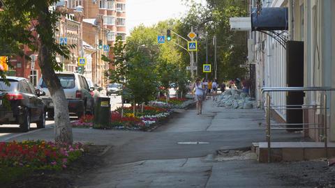 People walk along the sidewalk a quiet street Archivo