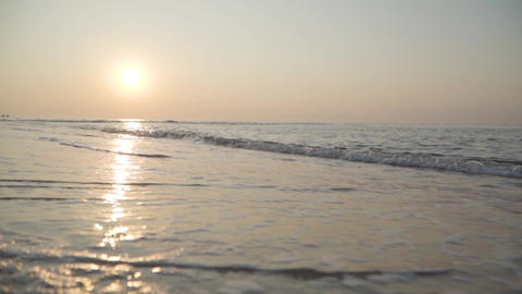 Calm waves of Mediterranean Sea rolling to the sandy beach at sunset. Beautiful Footage