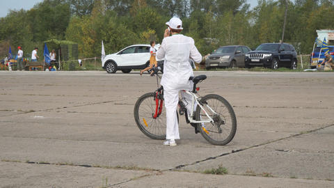 A woman in white clothes talks on the phone sitting on a Bicycle, and then Archivo