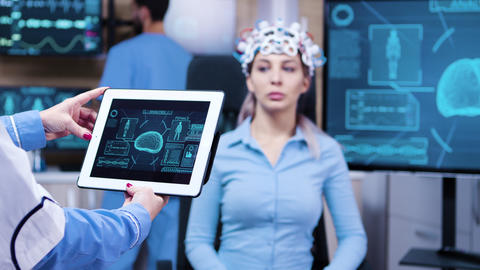 Female doctor looking at tablet with patient brain activty ビデオ