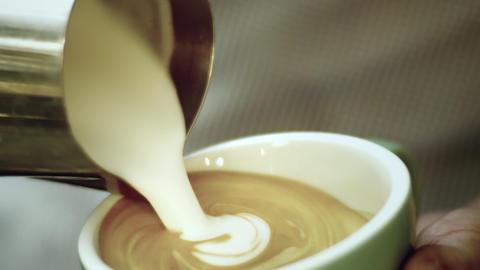 Barista prepares cappuccino in green mug Footage