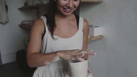 Smiling asian potter with clay pot GIF