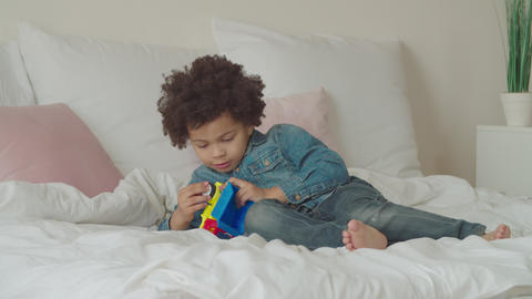 Serious cute little kid repairing toy car on bed GIF