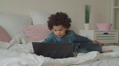 Multiethnic boy watching video online using laptop Footage