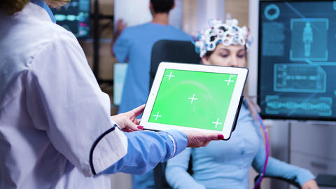 Female doctor holding tablet with green screen in a modern neurology lab science ビデオ