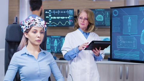 Female patient with eyes closed wearing headset with brains sensors ビデオ