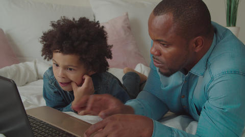 Father with child browsing online with laptop GIF