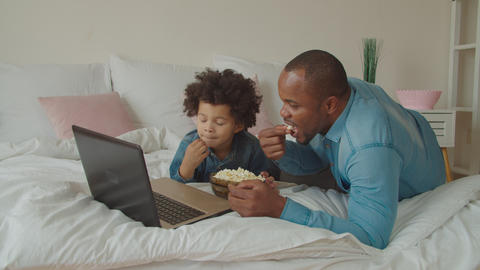 Family with popcorn streaming movie online on bed ビデオ