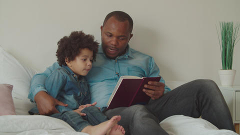 Black father reading story to little son on bed Archivo