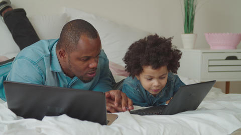 Caring black dad teaching son using laptop at home Live Action