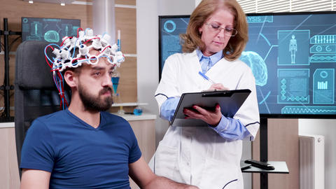 Female scientist in brain activity taking notes on her clipboard ビデオ
