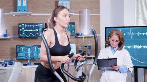 Female doctor mesuring the heart activity of female athlete Live Action