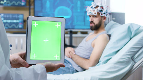 Doctor in a neurology clinic holding tablet with green screen ビデオ