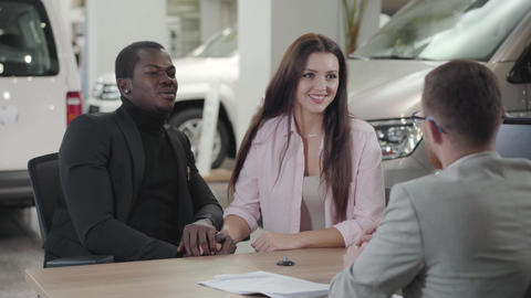 Young beautiful Caucasian woman talking to car dealer and holding husband's hand Footage