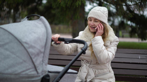 Young mother walks in autumn park with baby carriage and talks on phone GIF