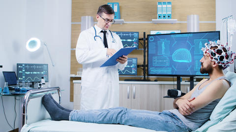 Doctor in a brain research laboratory checking on patient sitting on bed GIF
