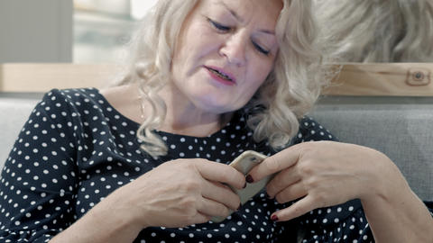 An old woman is recording a voice message on a smartphone. Modern technology for Live Action