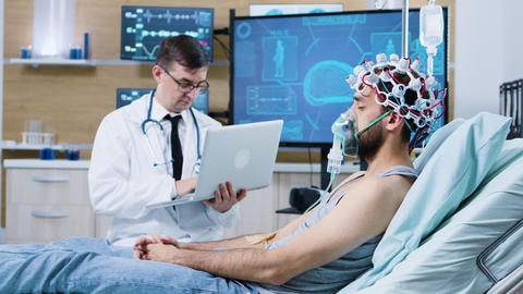 Doctor using his laptop in modern facility for brain analysis ビデオ