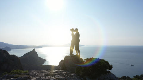 Aerial silhouette of a loving couple standing on the top of a mountain over the GIF