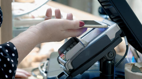 An old woman is paying in a cafe with a smartphone. Attaches a smartphone from Live Action