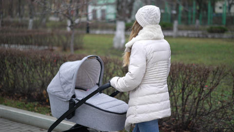Young mother walking with a child in pram. Autumn season GIF