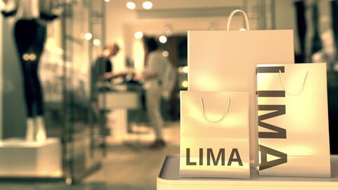 Shopping bags with LIMA text against blurred store. Peruvian retail related clip Footage