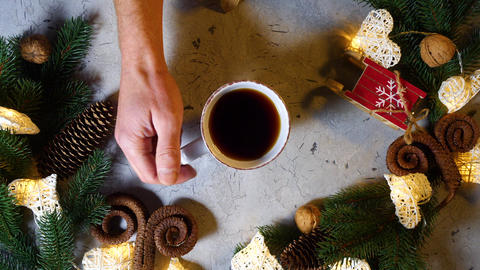 Cup of black tea or coffe on the New Year's table, which is taken by male hands GIF