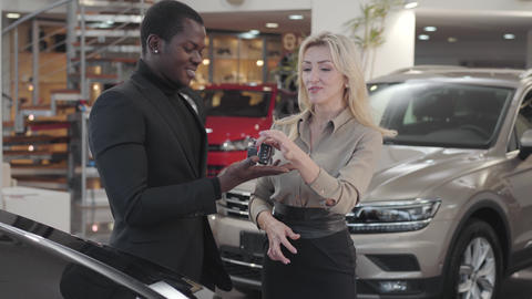 Pretty Caucasian woman giving car keys to the African American man in automobile Footage