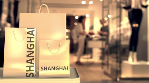 Shopping bags with SHANGHAI text against blurred store. Chinese retail related GIF