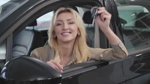 Satisfied Caucasian blond woman with brown eyes bragging car keys while sitting Live Action
