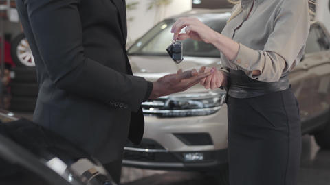 Close-up of female Caucasian hand giving car keys to African American buyer Live Action