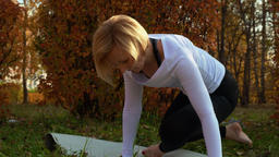 Fitness woman stretching body on carpet on outdoor workout in autumn park. Sport Footage