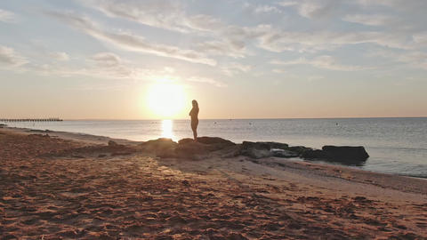 Silhouette of a woman who stands on the seashore at dawn The camera slowly GIF