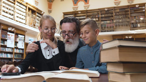 Happy senior bearded granddad reading exciting book to his smiling teenage Archivo